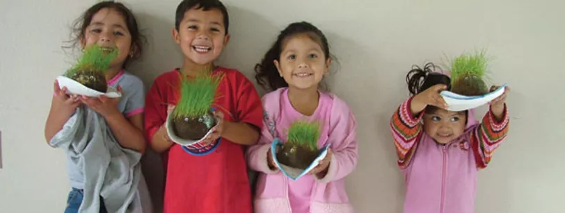 Four young children holding seed heads, learning patience by growing grass hair in sod.