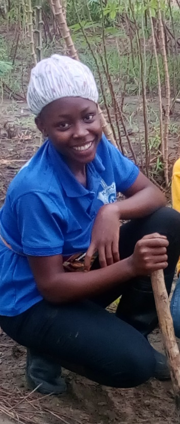 A student smiles with her farming tool.