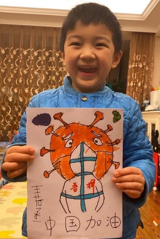 A child is beaming with happiness holding their drawing.