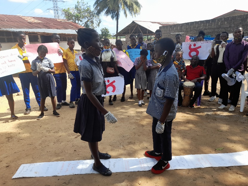 Students face each other on a project mat.