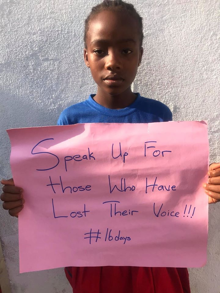 A young girl holds up a poster that reads, speak up for those who have lost their voice! #16days