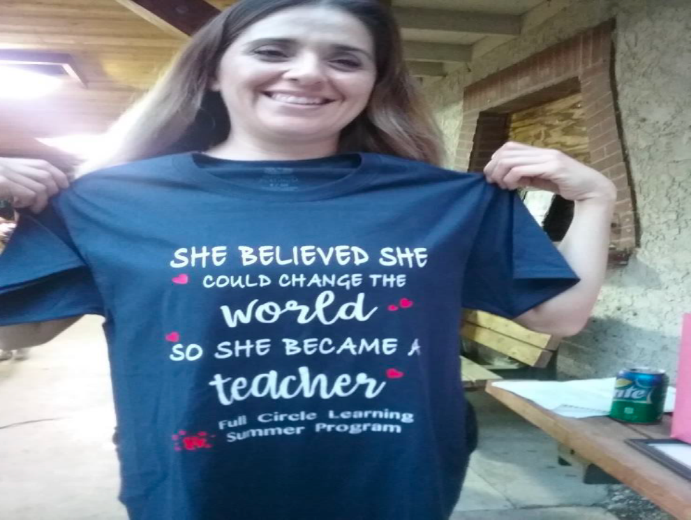 Woman with t-shirt that reads She believed she could change the world so she became a teacher