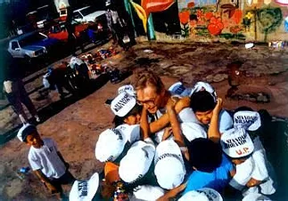 A man is crowded by several children in celebration of painting neighborhood walls