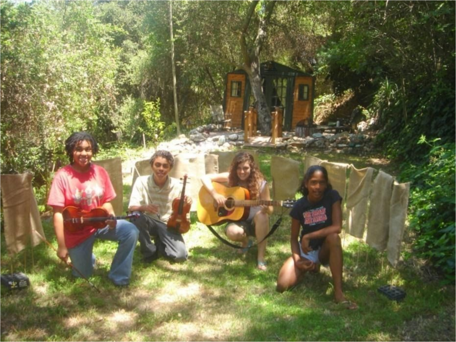 Four students performing with instruments