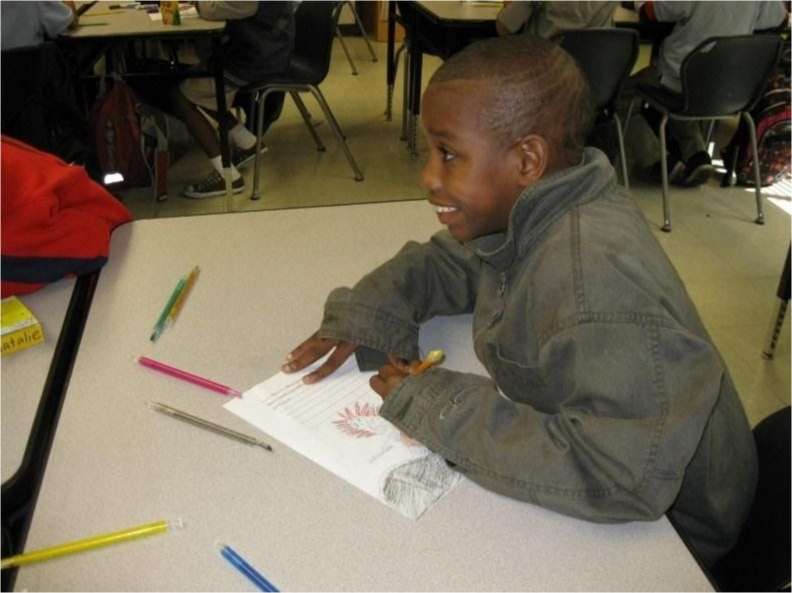 An academy student smiles while drawing an assignment.