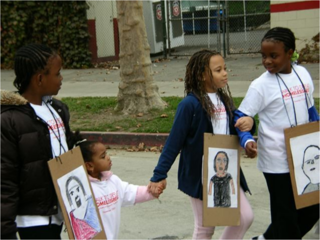 Young students hold hands walking with signs