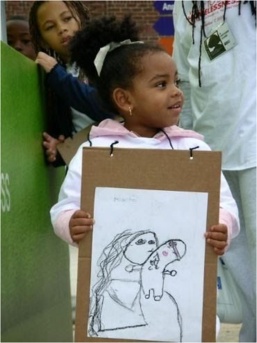 A young girl holds her drawing up
