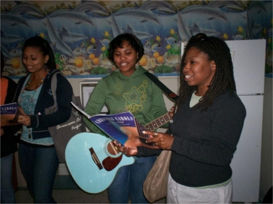 Three students sing and play guitar in front of the class