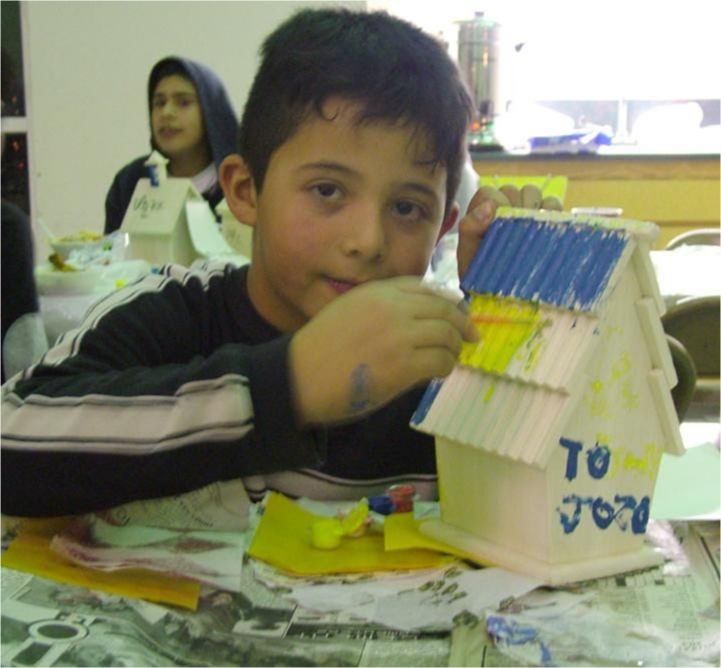 A student builds a model house out of crafts