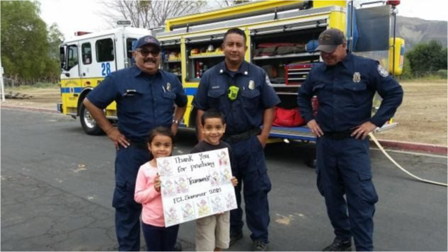 Children present a sign to firefighters