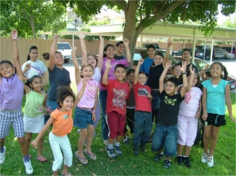 A classroom of children wave and smile at the camera under a tree.