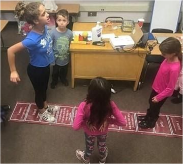 Kids in class play a jumping game.