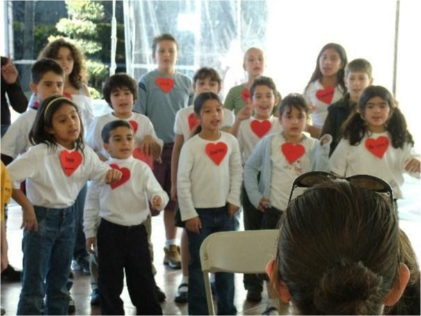 A class of kids singing to medical researchers.