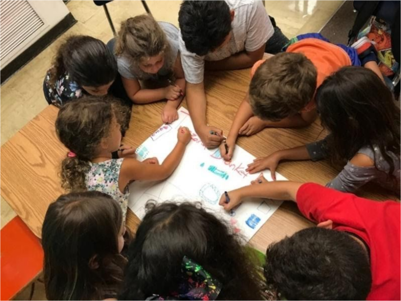 A group of kids drawing on the same sheet of paper.
