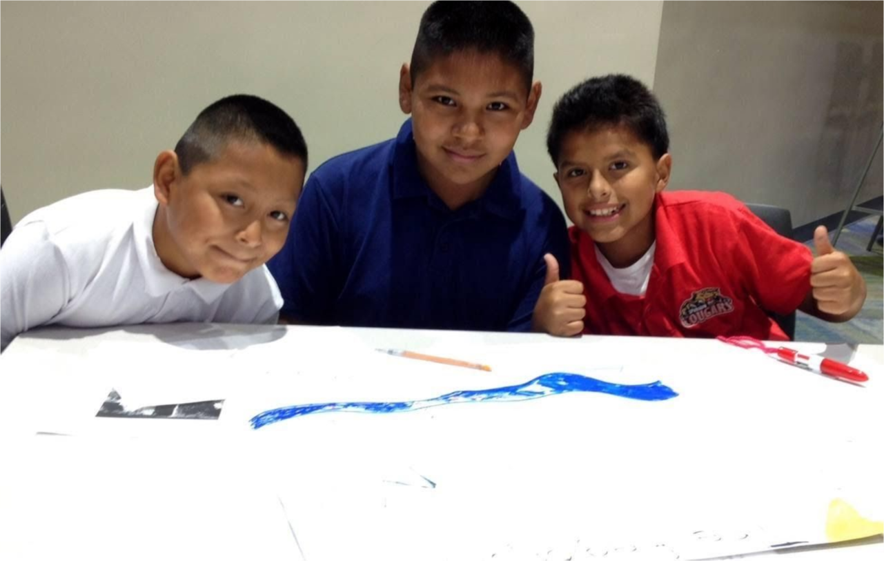 Three students proud to be together with their art on the table.