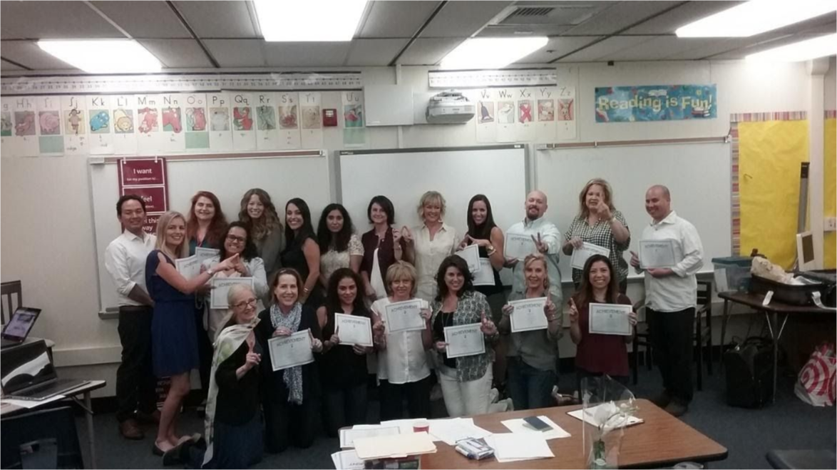 Teachers at a training workshop with their certificates.