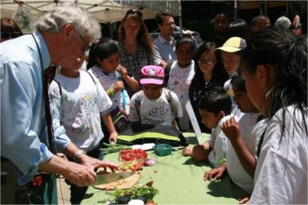 A class outside cutting vegetables while talking nutrition.