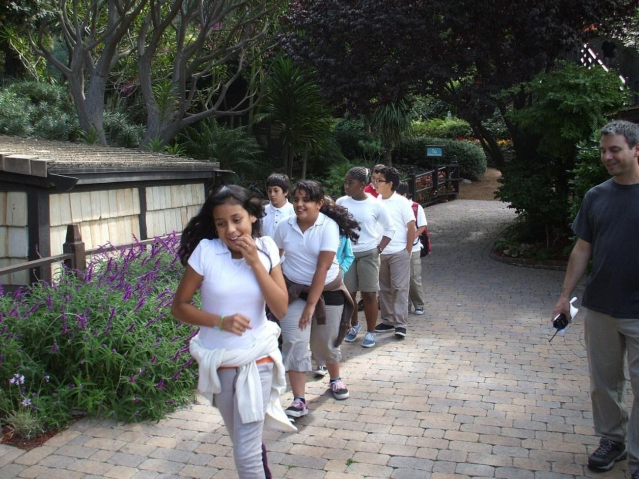 A row of students move through gardens.