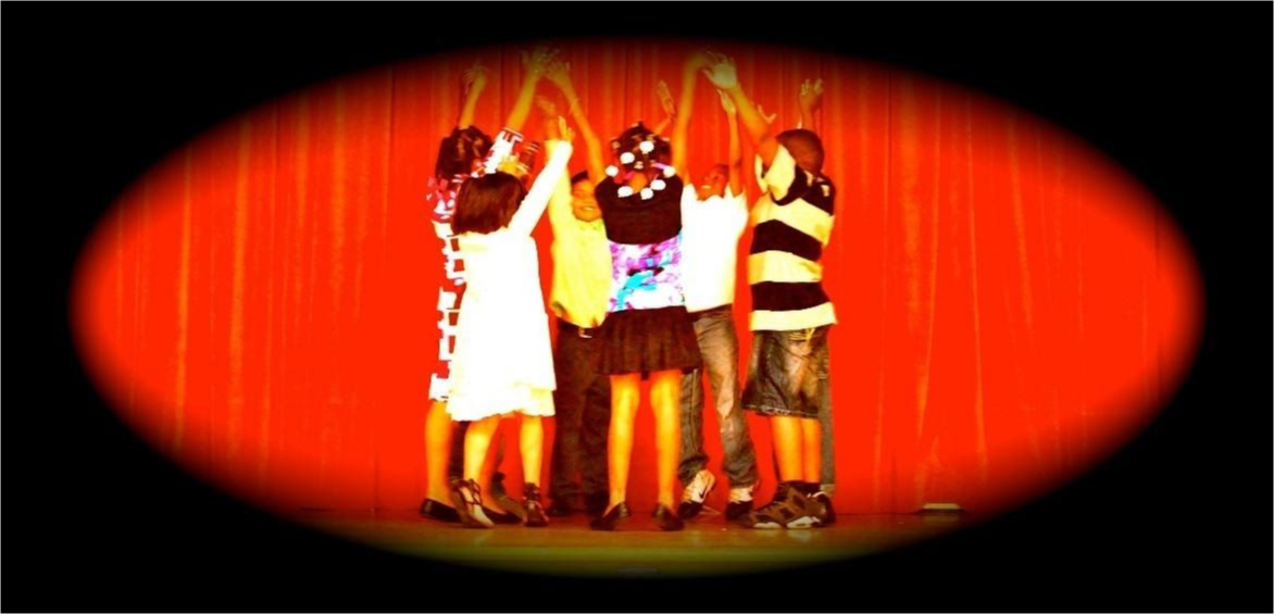Children raise their arms in a circle on stage.
