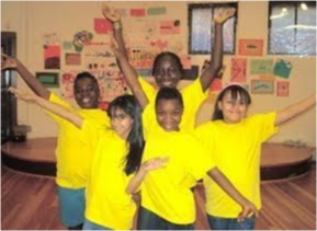 Young members of the Children's theater company in bright yellow shirts.