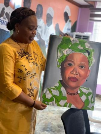 A woman presents a painting while talking.