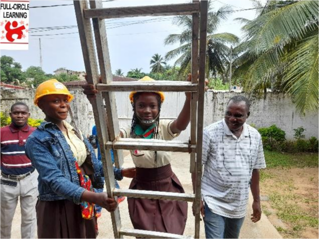 A student begins to climb a ladder assisted by her Teacher.