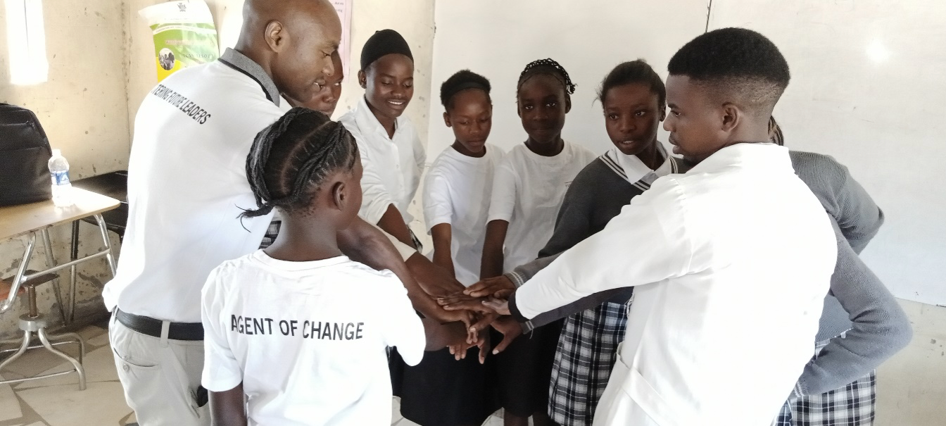 Teacher and students form a all hands in circle.