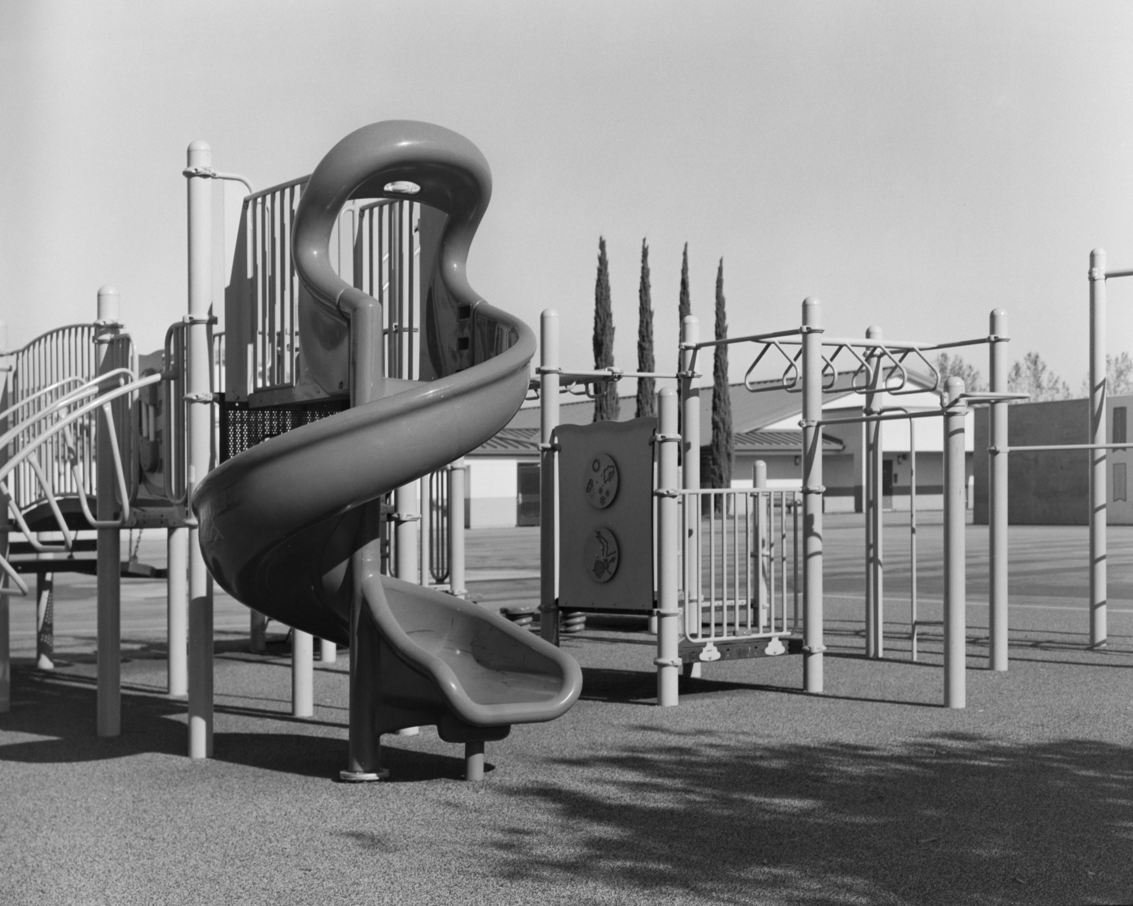 A black-and-white photograph of an elementary school playground, featuring a spiral slide.