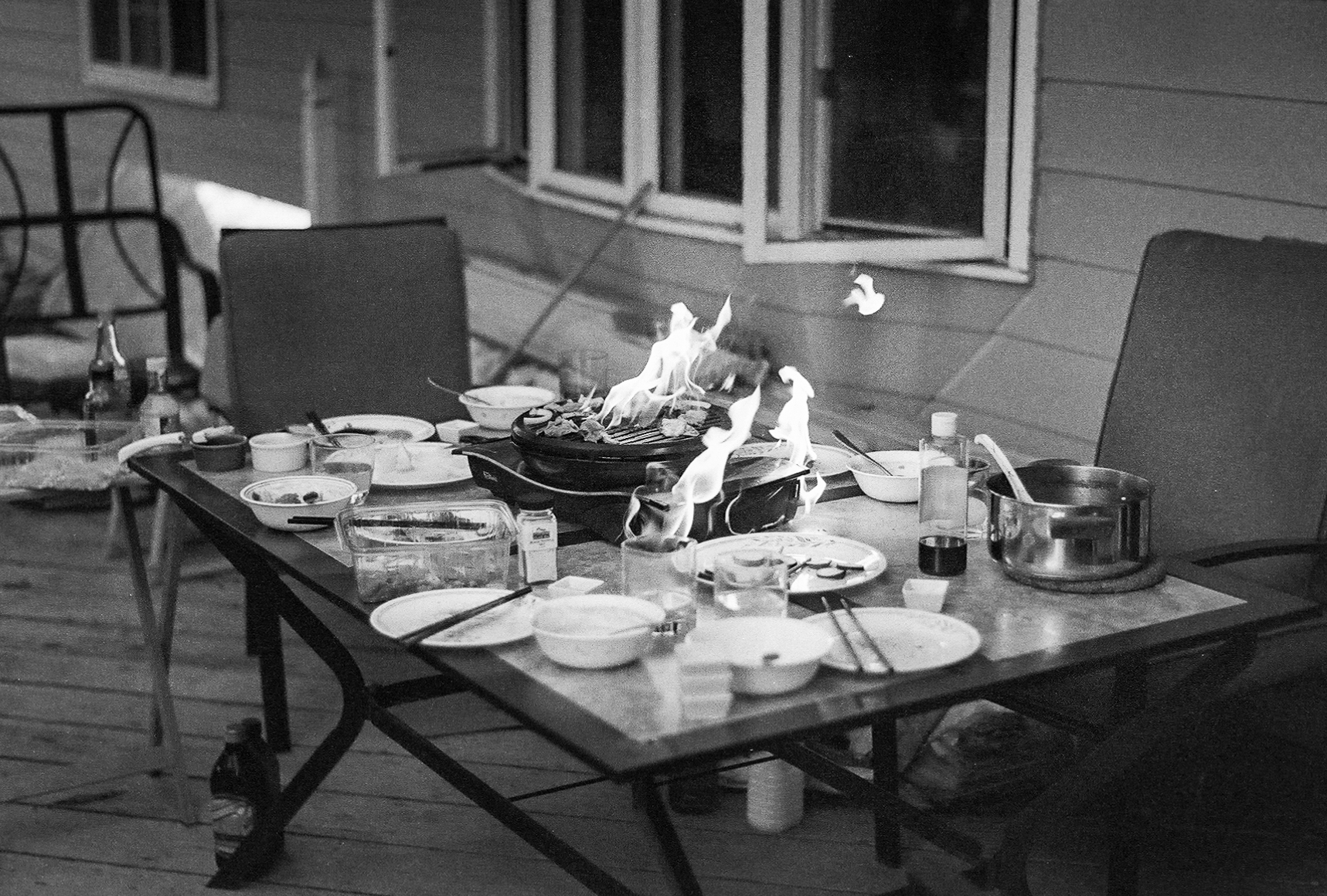 An outdoor dining table, with dishes, utensils, and a portable gas stove, which is engulfed in flame.