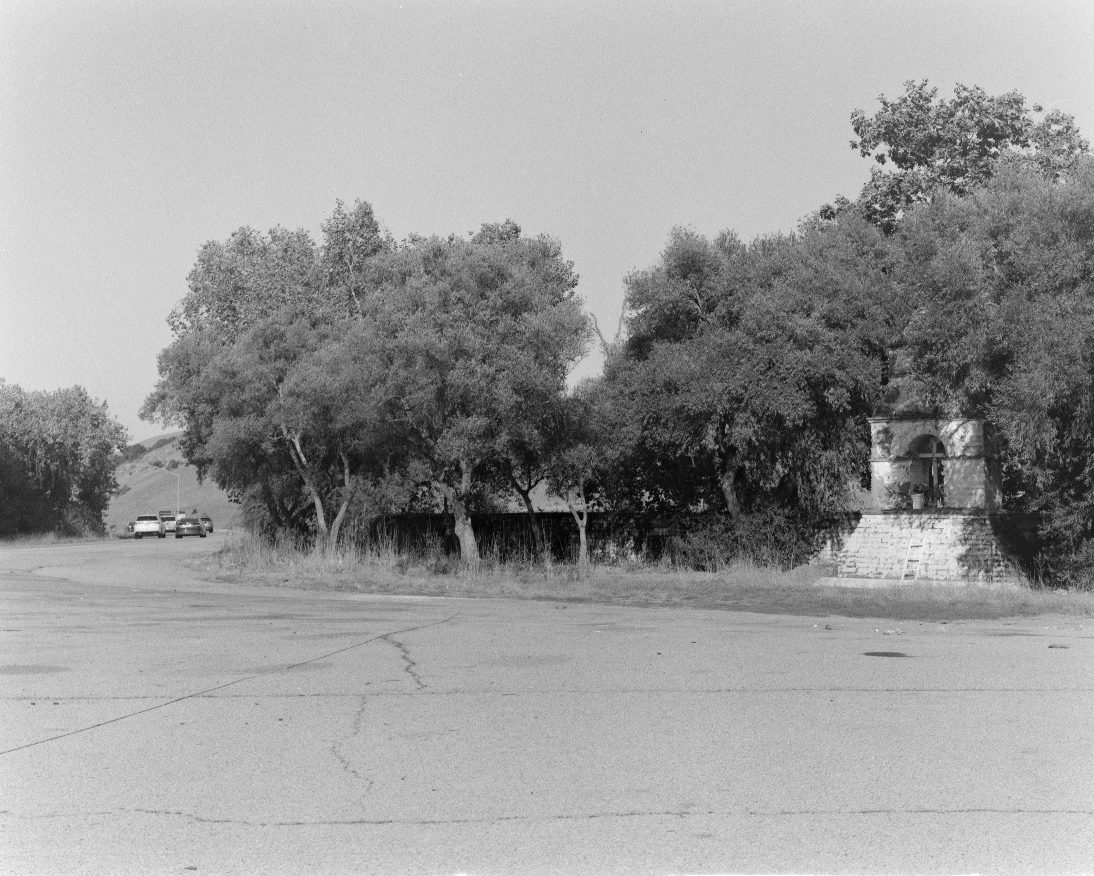A black-and-white photograph of a dilapidated mission monument underneath a stand of trees. It contains a cross, and is adorned with flowers in pots. A busy highway filled with cars runs past the ignored monument.