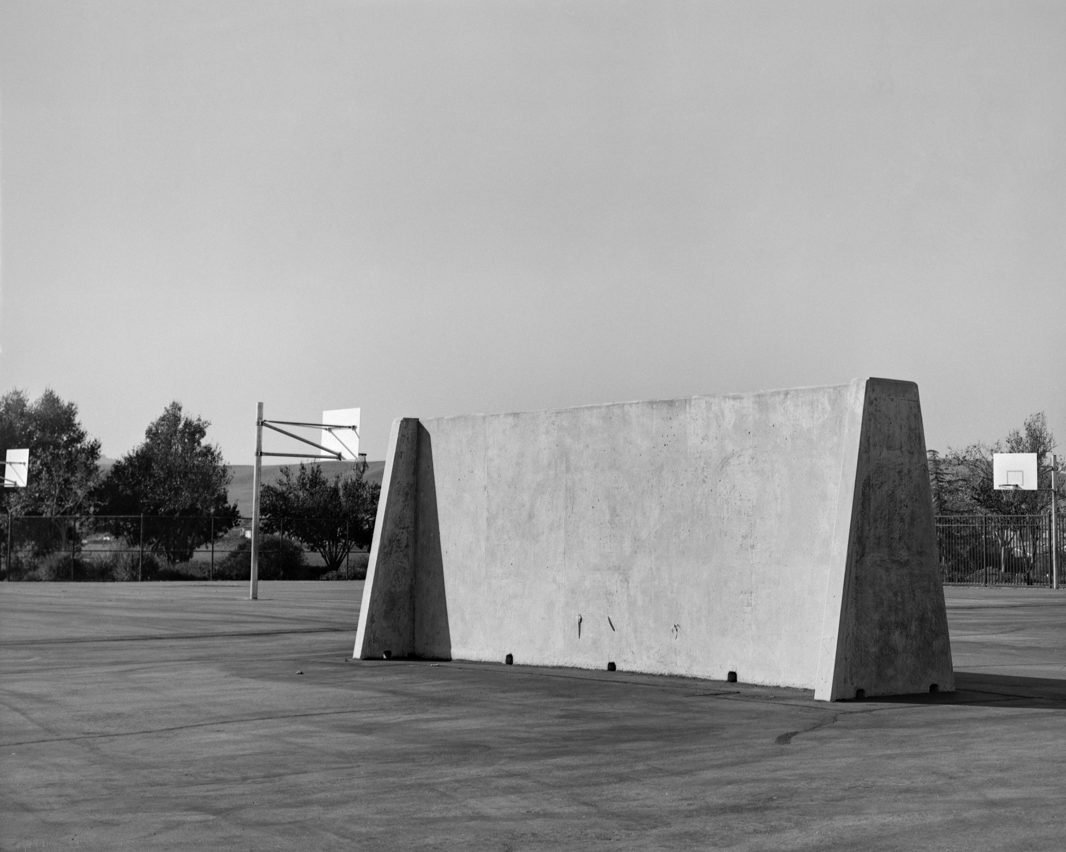 A black-and-white photograph of a wall ball court, featuring a free-standing cement wall. It sits in the middle of an empty asphalt school yard, in front of basketball hoops, fencing, and trees.