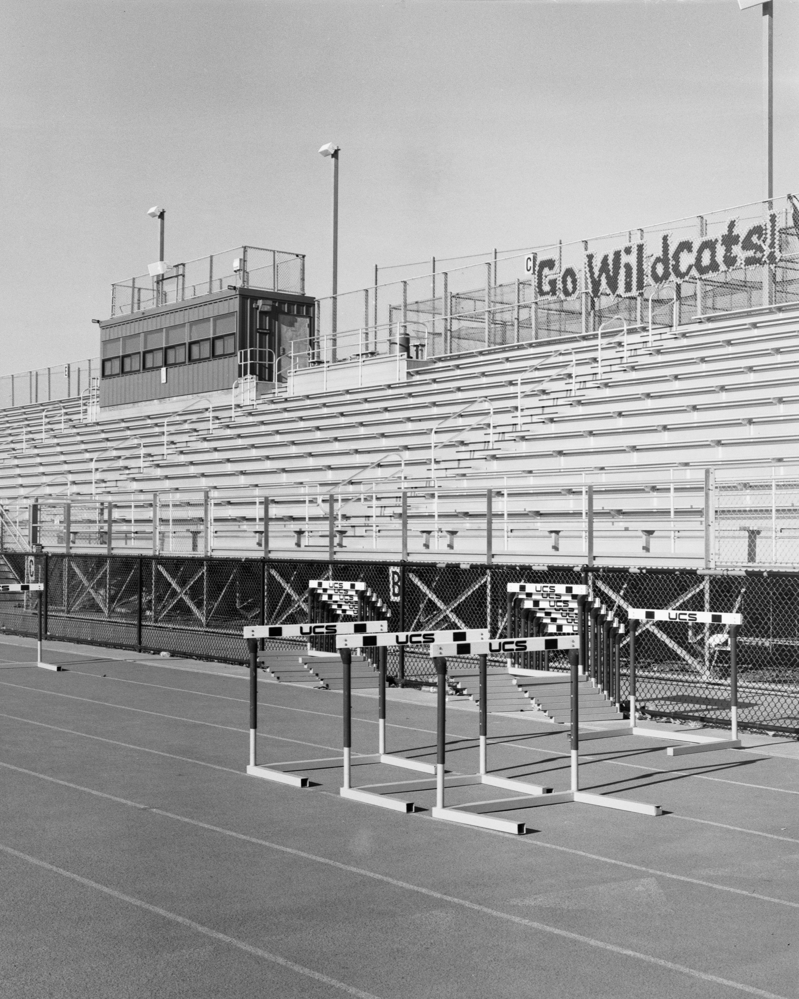 """A black-and-white photograph of several hurdles sitting on a high school running track. Behind them are bleachers, several stories tall. A display on the fence at the top of the bleachers spells out """"Go Wildcats!"""""""