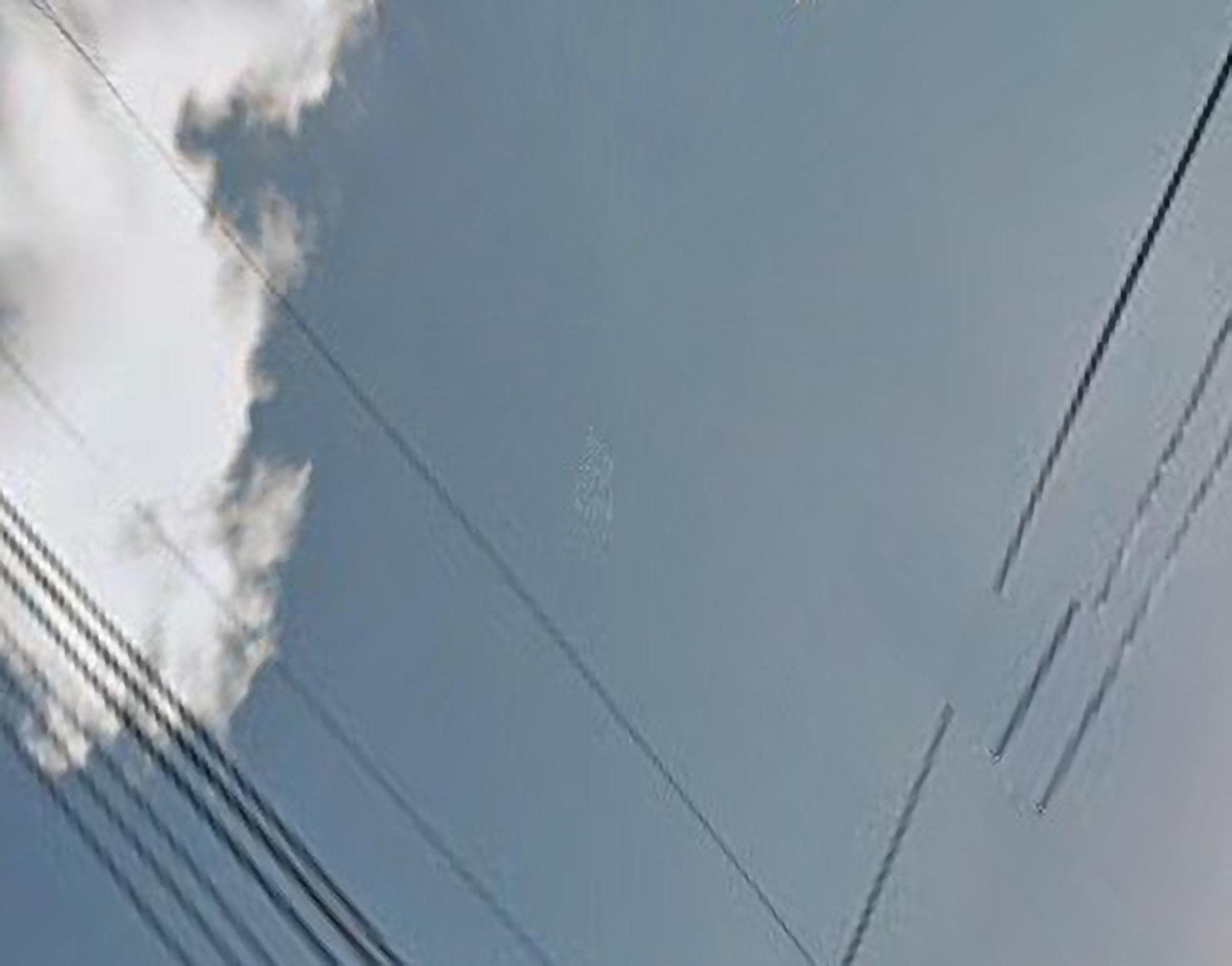 "An abstract photograph of clouds against a blue sky, with distorted power lines criss-crossing the image in a ""V"" pattern."
