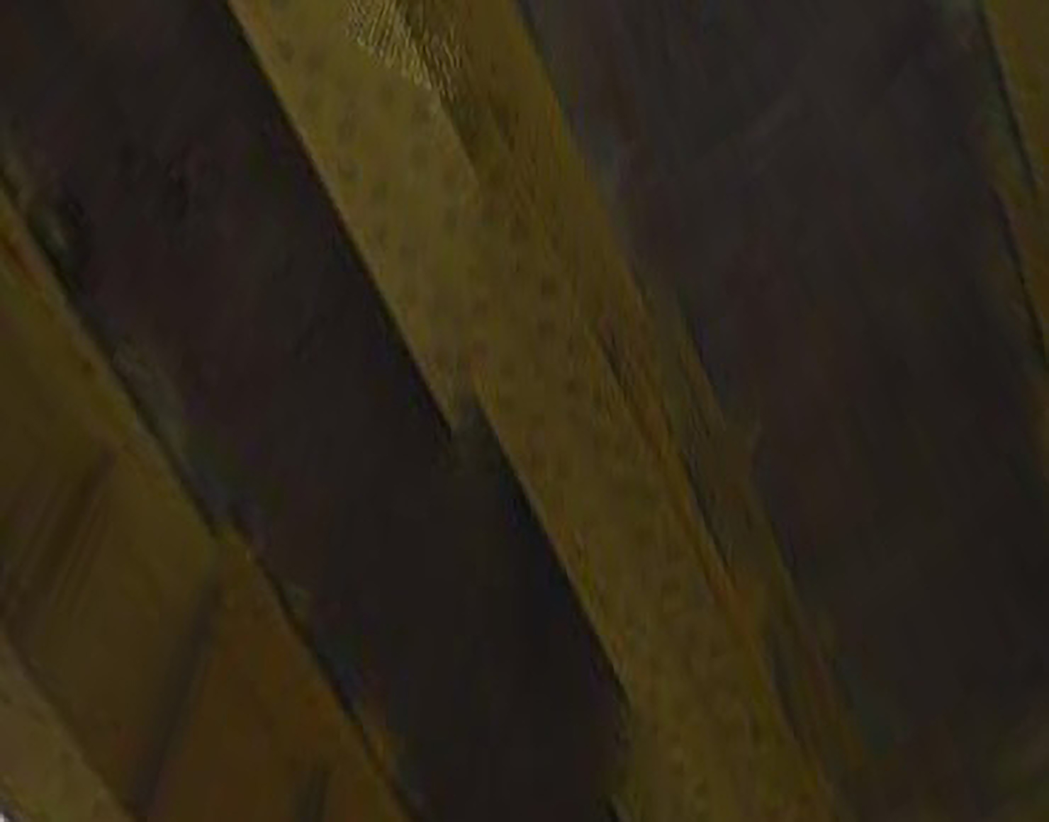 An abstract photograph of the underside of a yellow bridge, built out of riveted steel.
