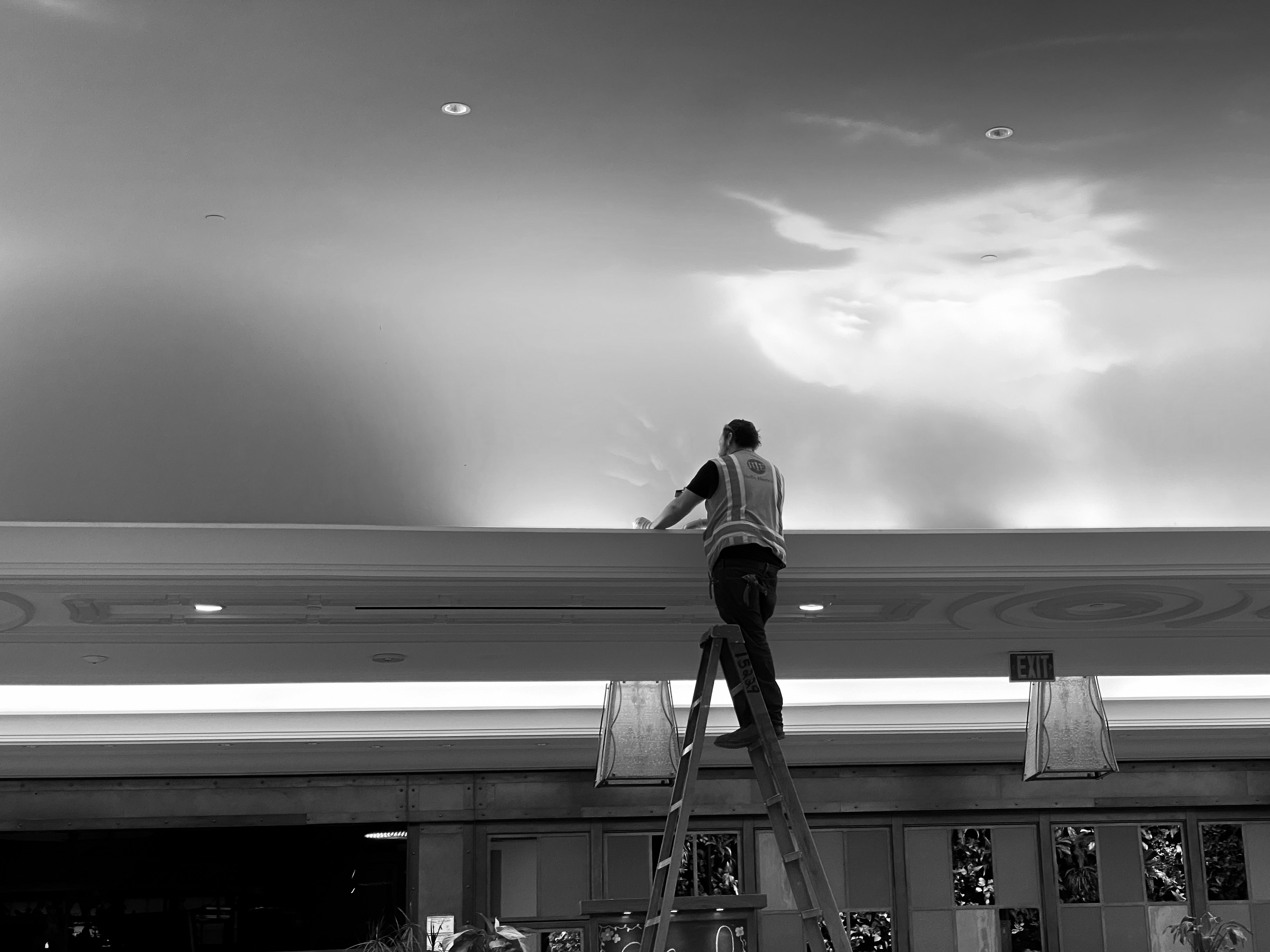 A construction worker works on lights illuminating an artificial painted sky.
