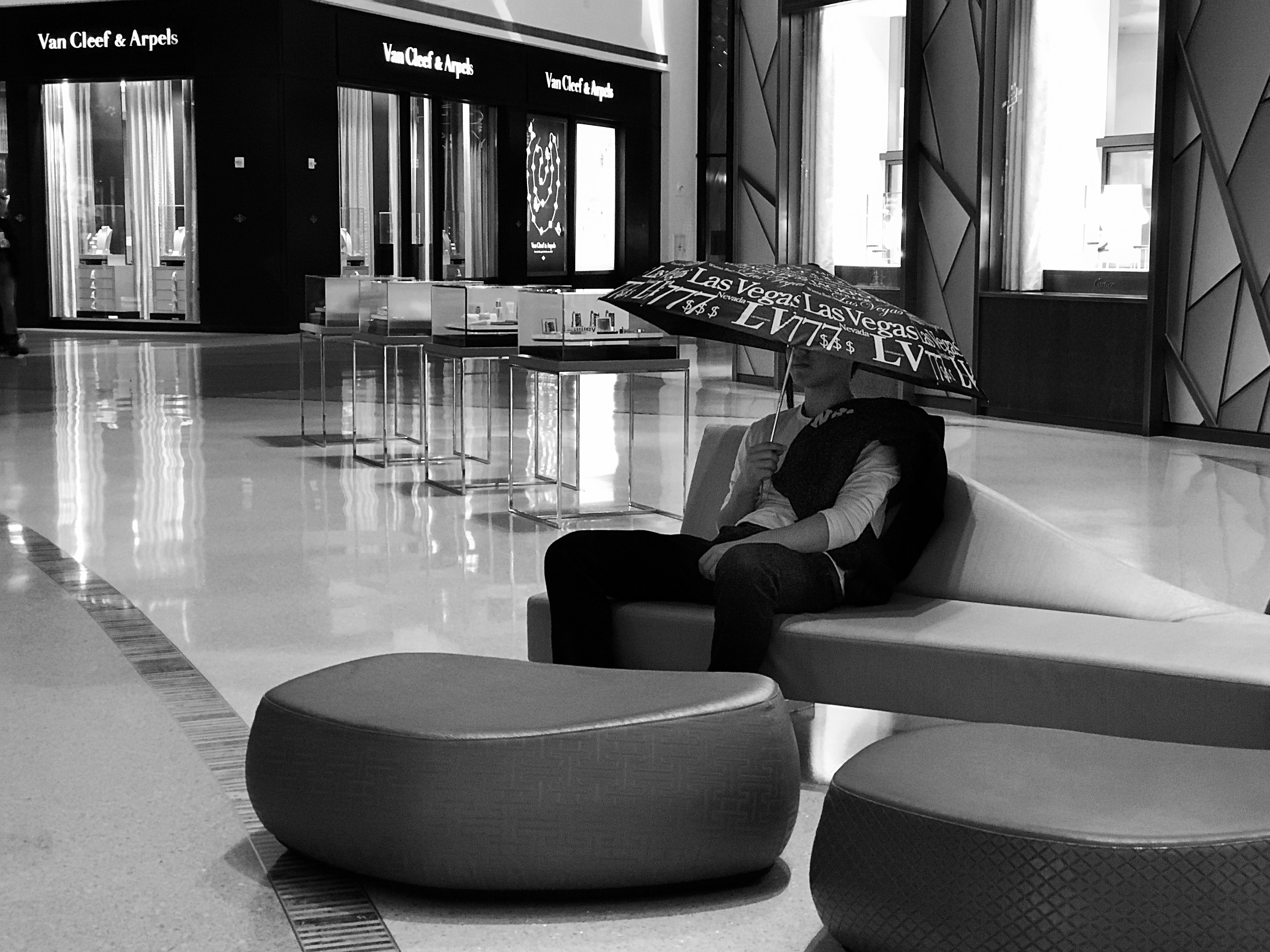 A boy sits on a couch in the middle of a large, shiny indoor mall, holding an incongruous umbrella low over his eyes.