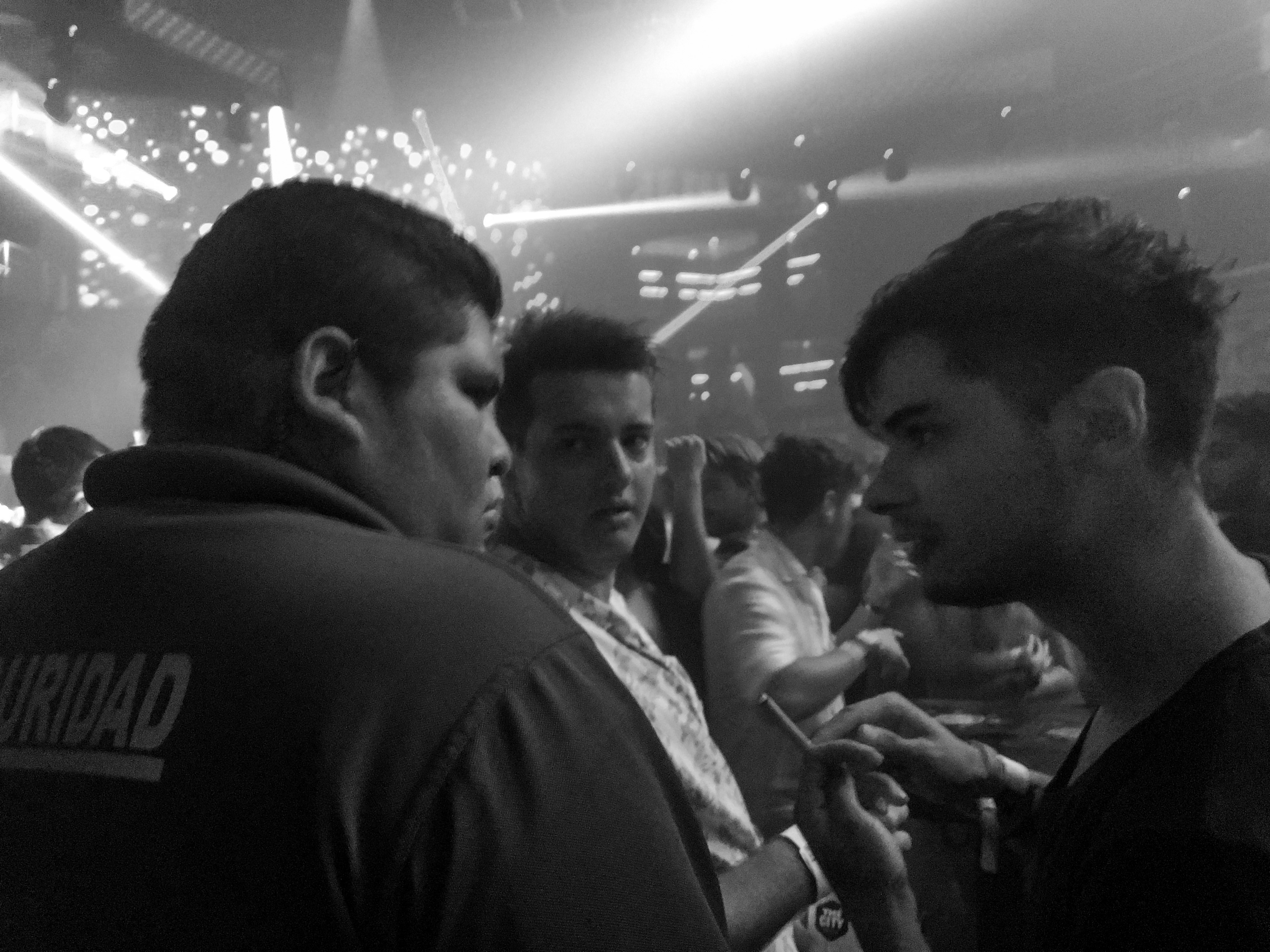 A large security guard confronts two college boys in a nightclub, one of whom is smoking a cigarette.