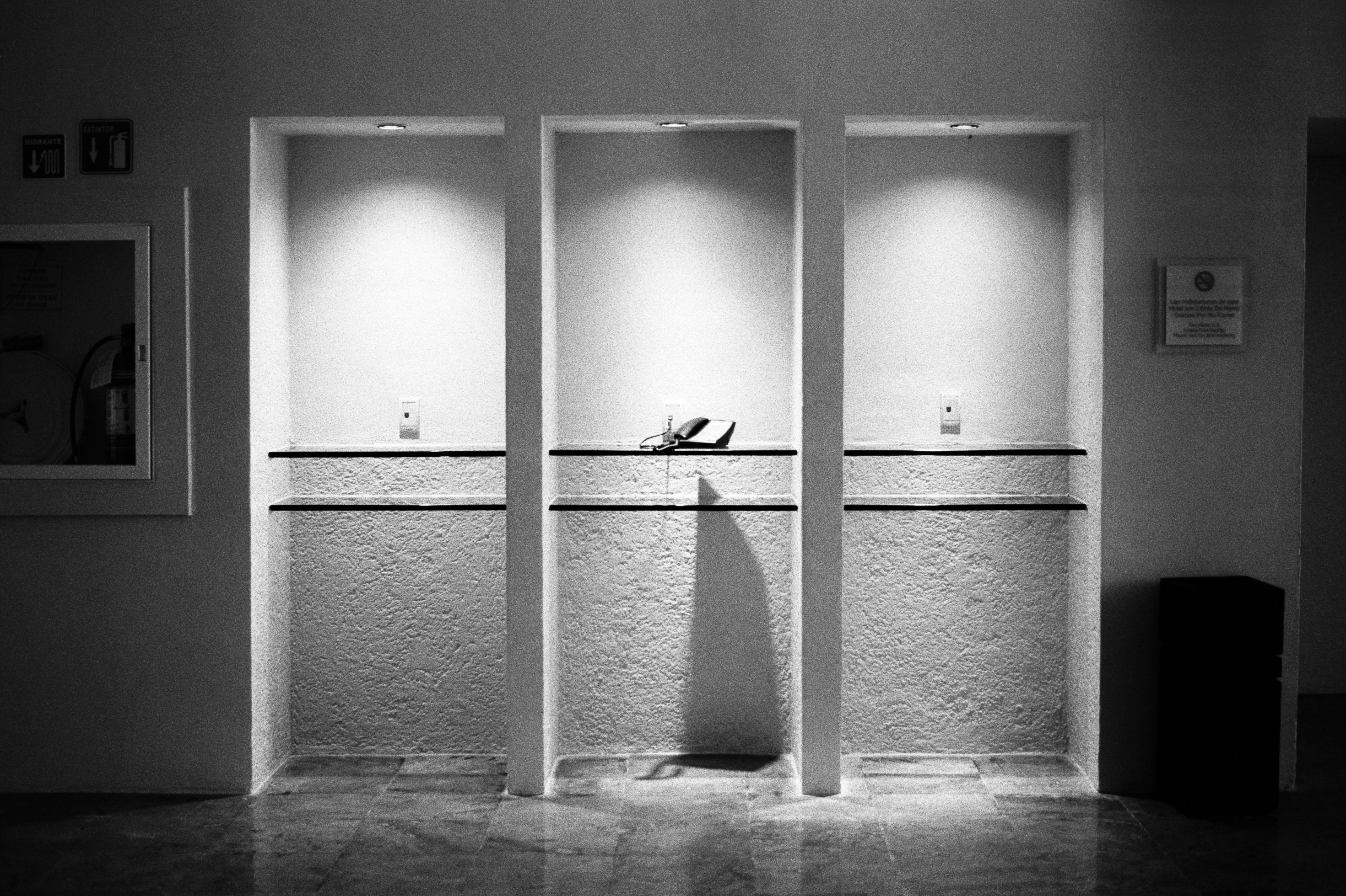 A wall of three empty hotel phonebooths sits empty, except for a single telephone. It sits on the glass shelf of the center booth, casting a long shadow down onto the wall and floor.