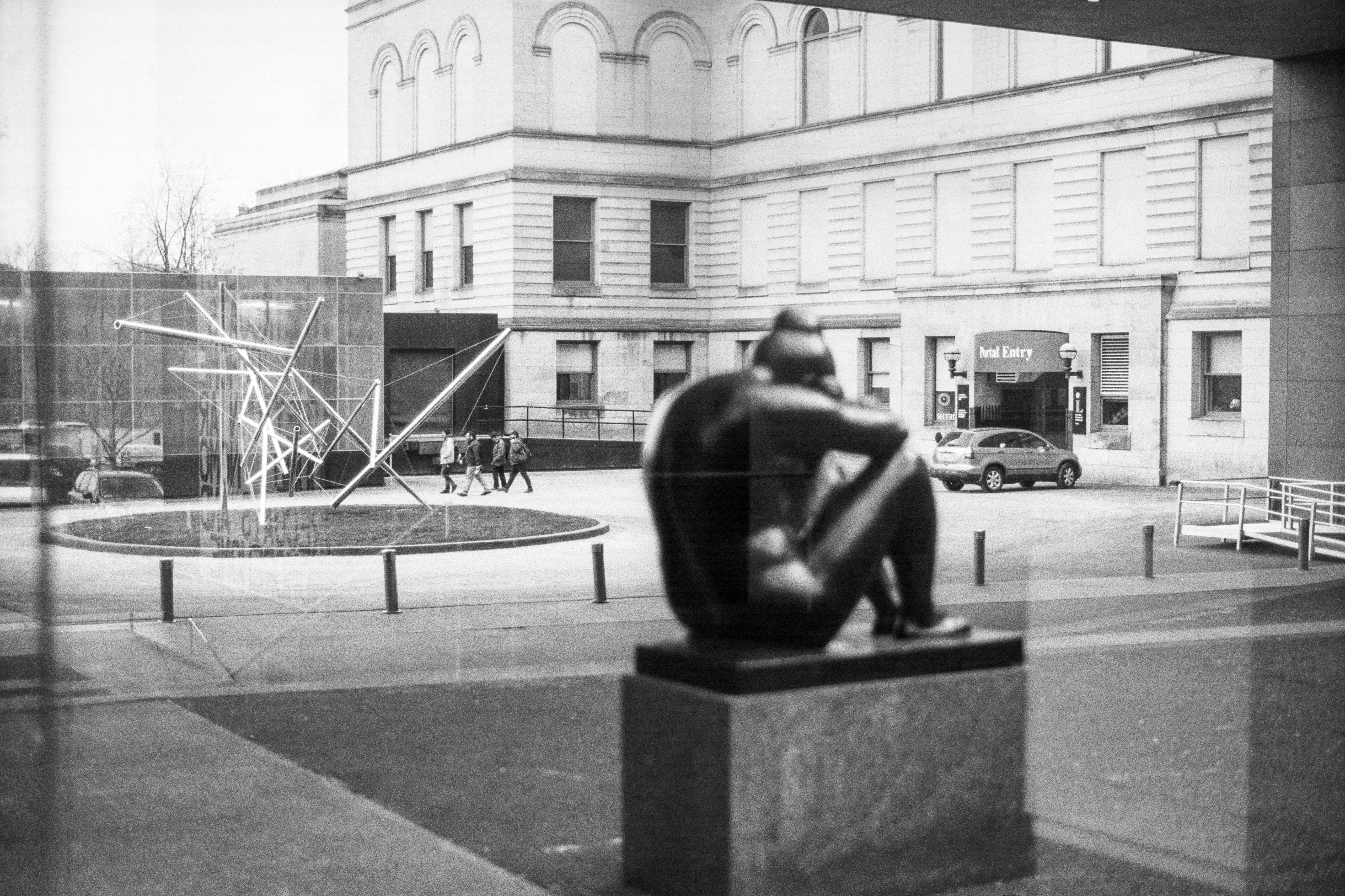 A sculpture of a woman sitting head-down in the fetal position sits in a sculpture garden. Behind it, a group of four people walk across a parking lot, next to a tangled artwork of pipe and cable.