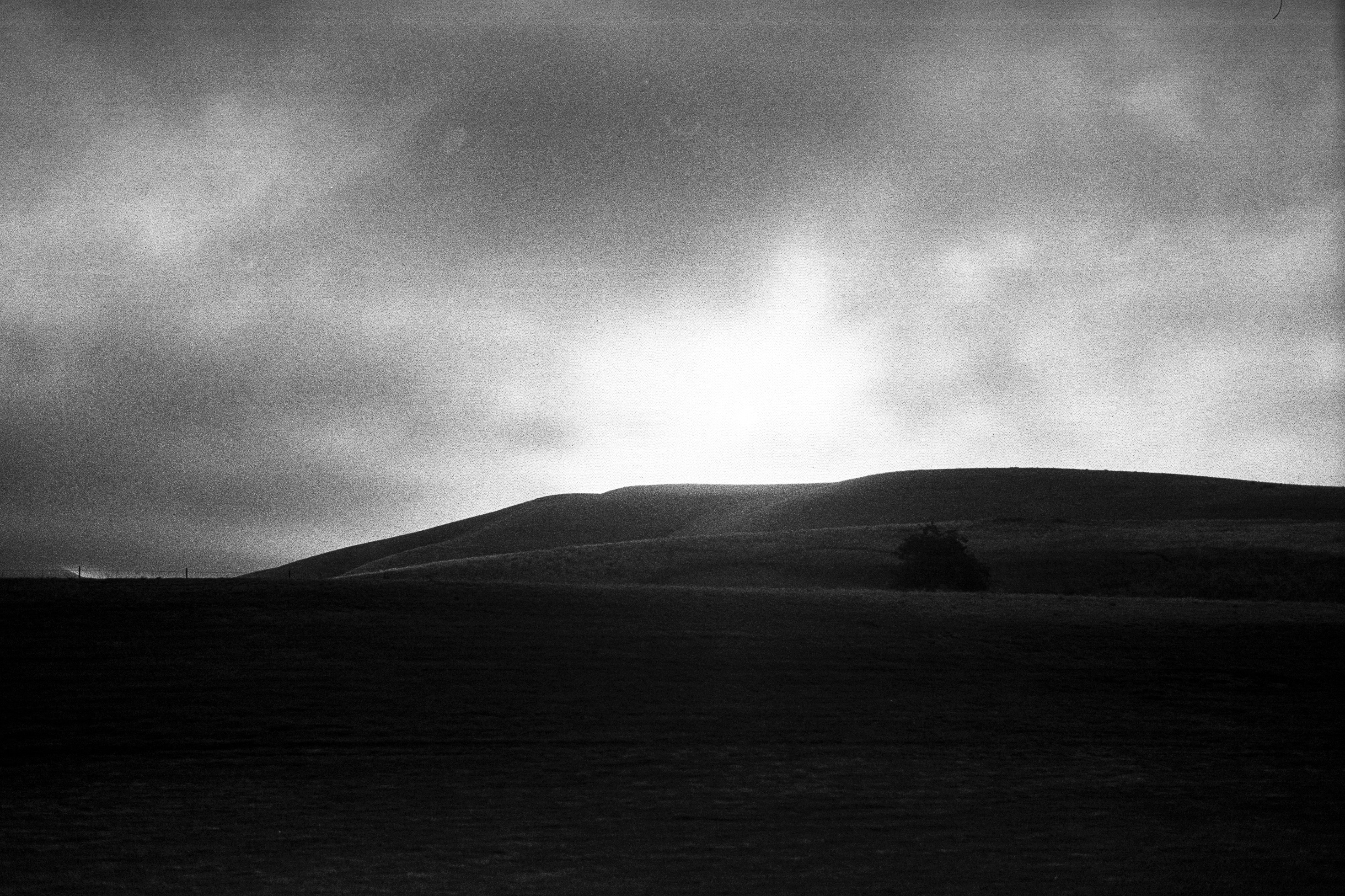 The sun rises against a backdrop of clouds, over a barren, ominous hill.