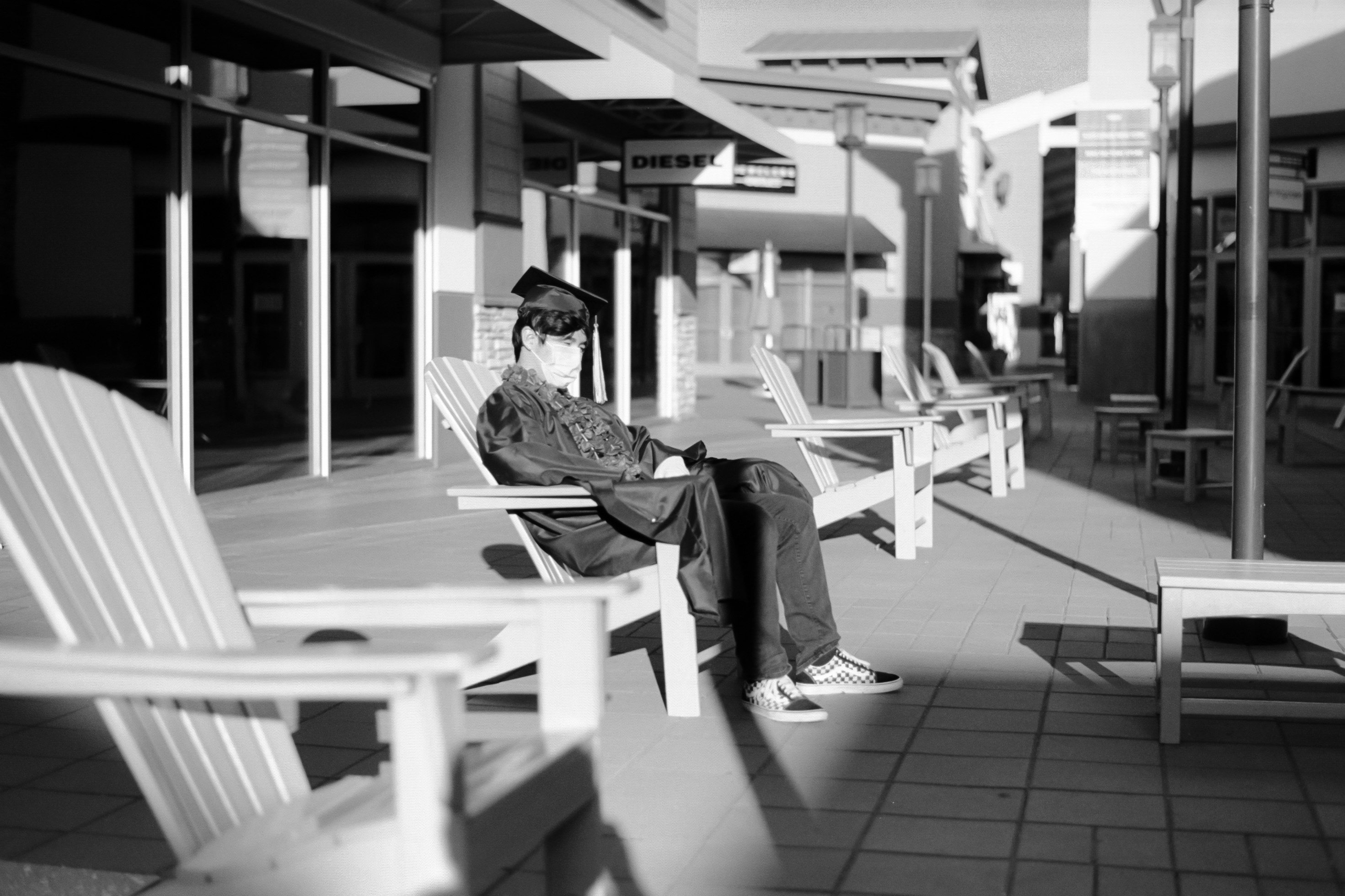 A boy sits alone among a row of lawn chairs in an abandoned shopping plaza. He is wearing full graduation regalia and a surgical face mask.