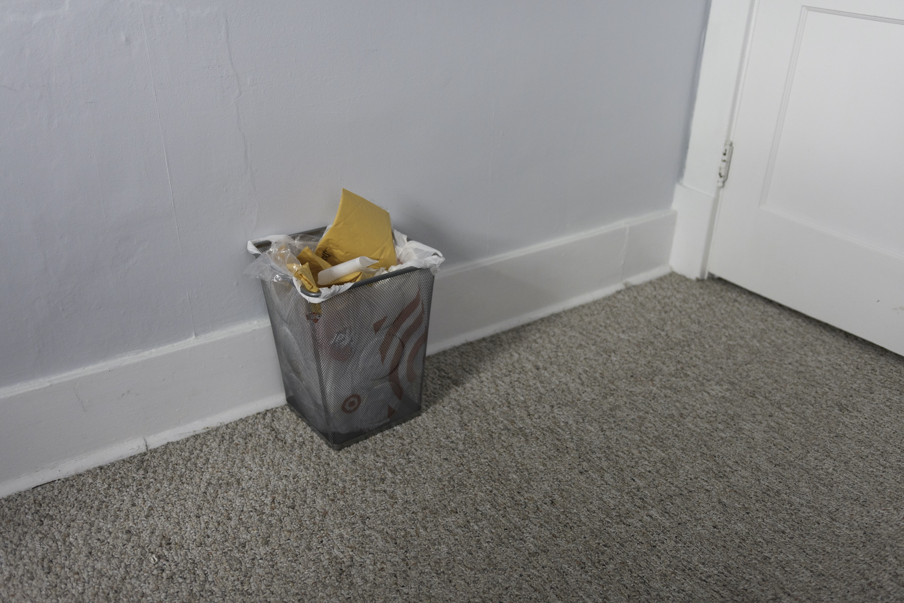 A small trashcan filled with yellow garbage sits on a beige carpet against a blue wall, next to a whitee door.