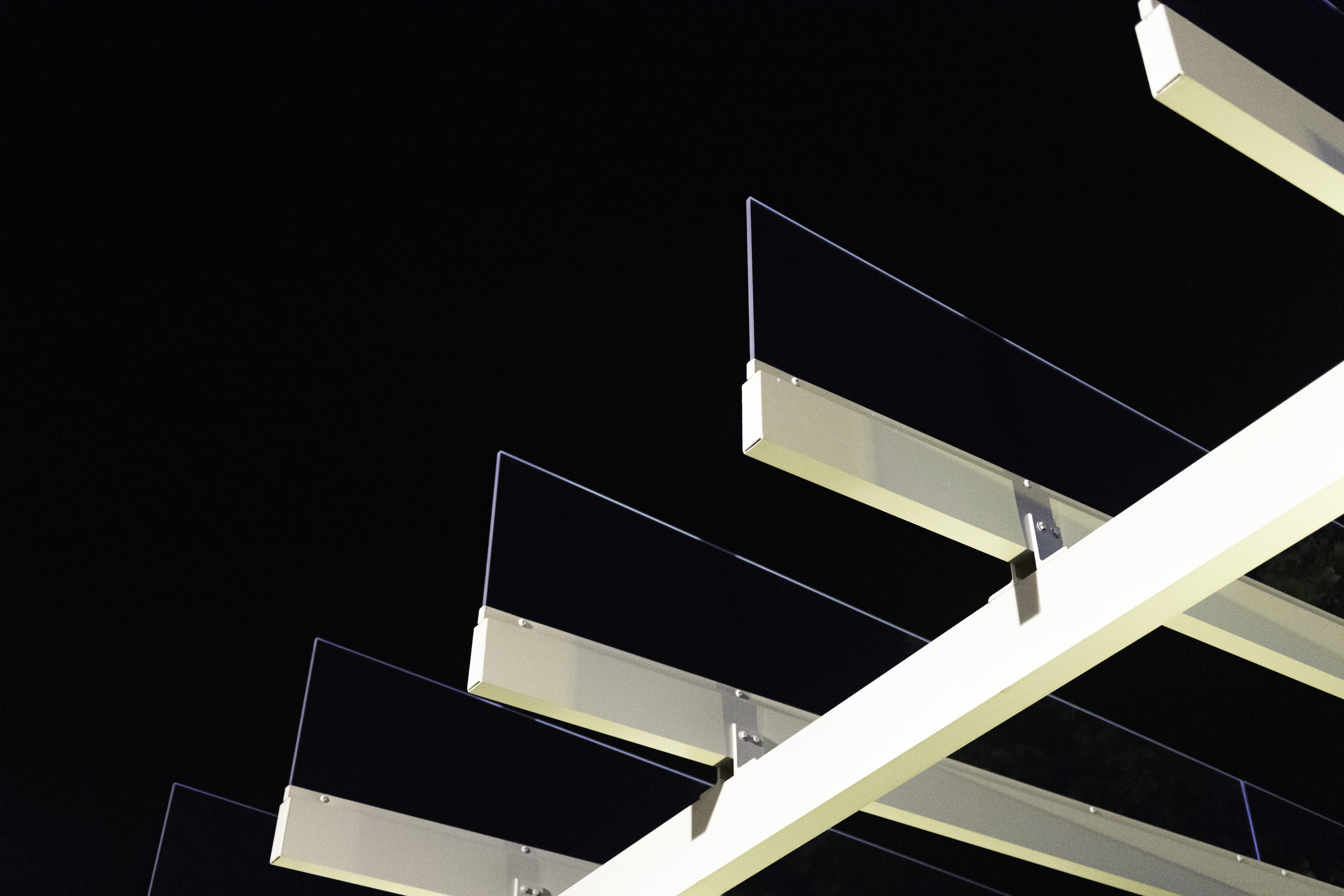 The beige metal and glass rafters of a modern pavilion jut violently into the frame, against a pitch-black sky.