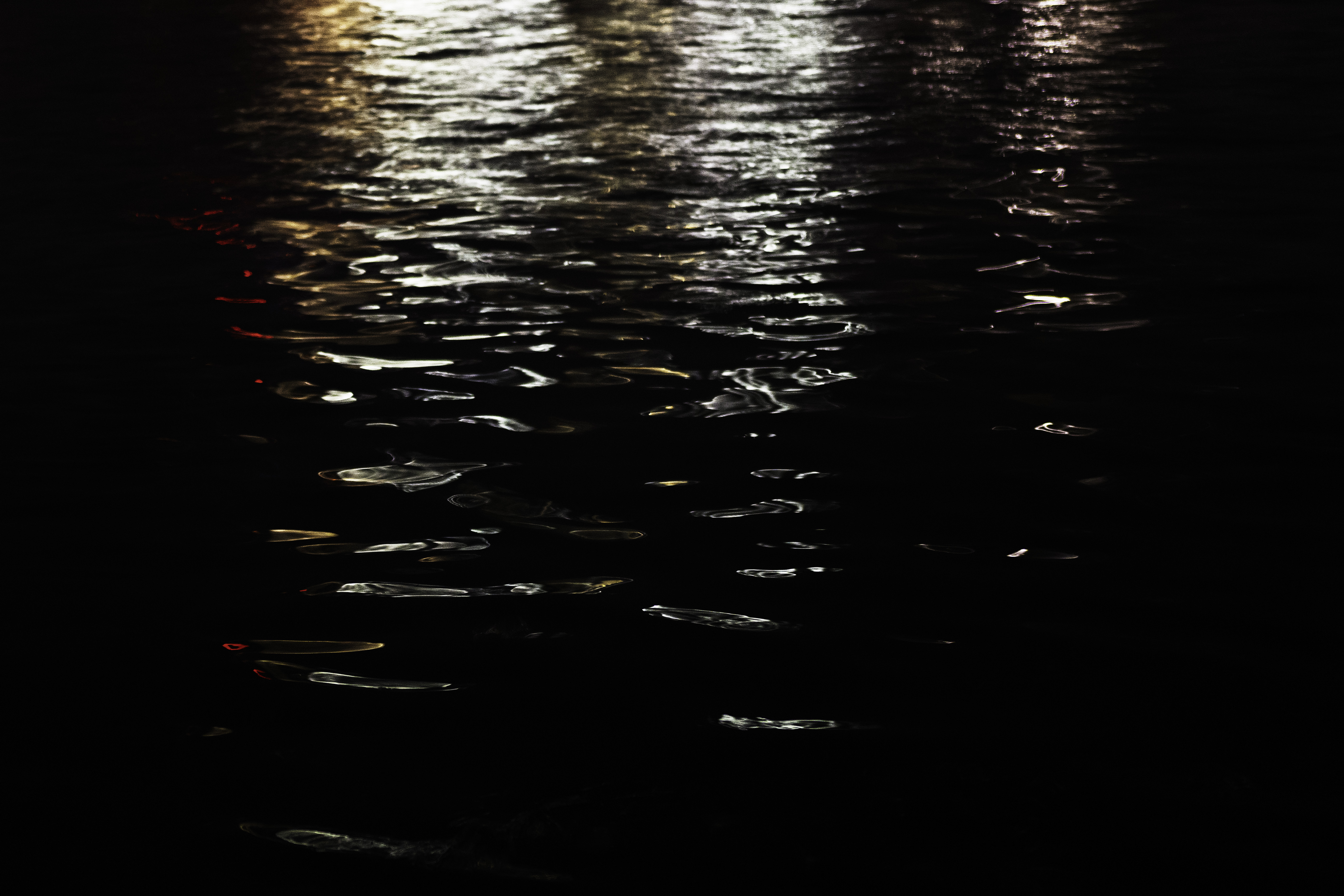 White, amber, and red lights bounce off of pitch-black water.