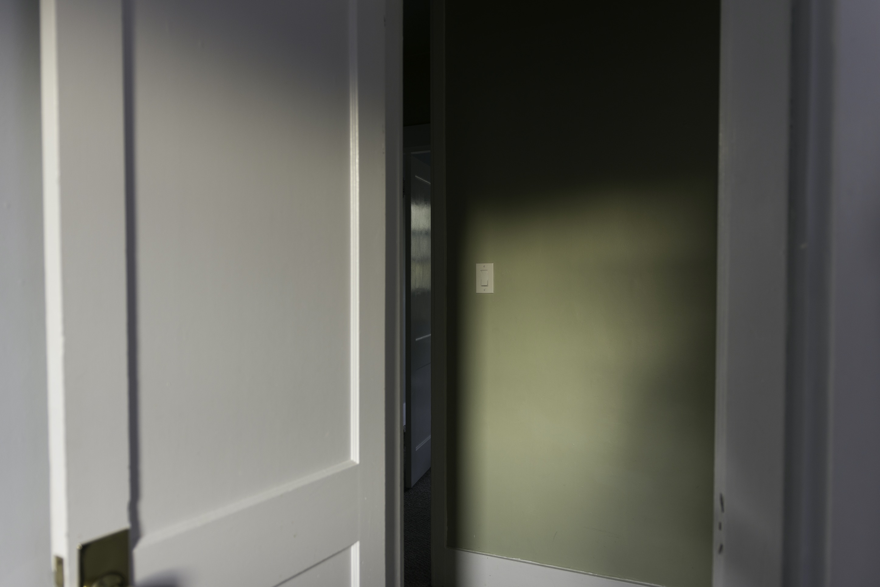 The image peeks down a hallway diagonally, through a few doors. The wall is bathed in soft, comforting light.