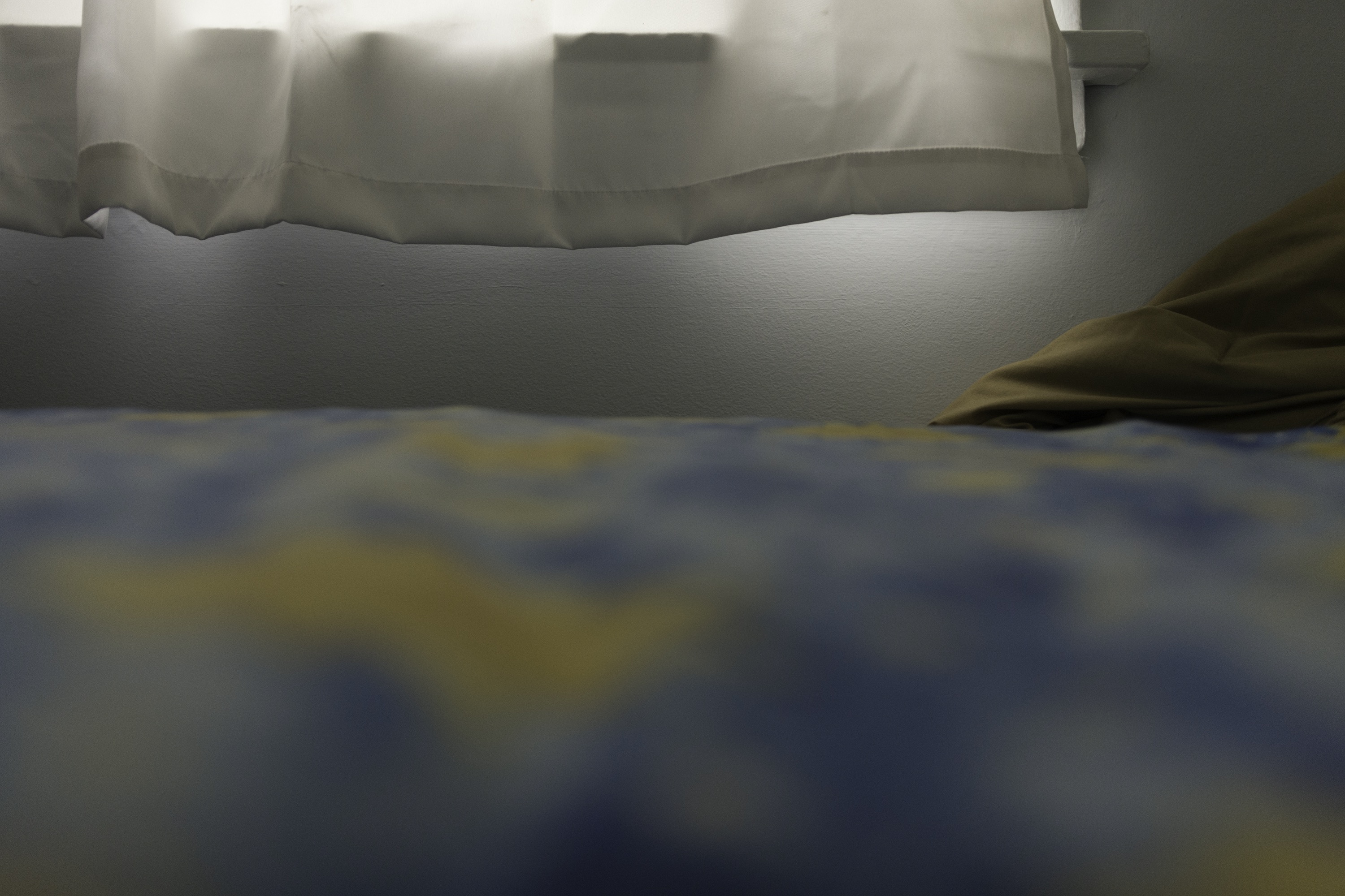 An out-of-focus yellow-and-blue bedsheet leads up to a window, which casts blobs of soft light downward.