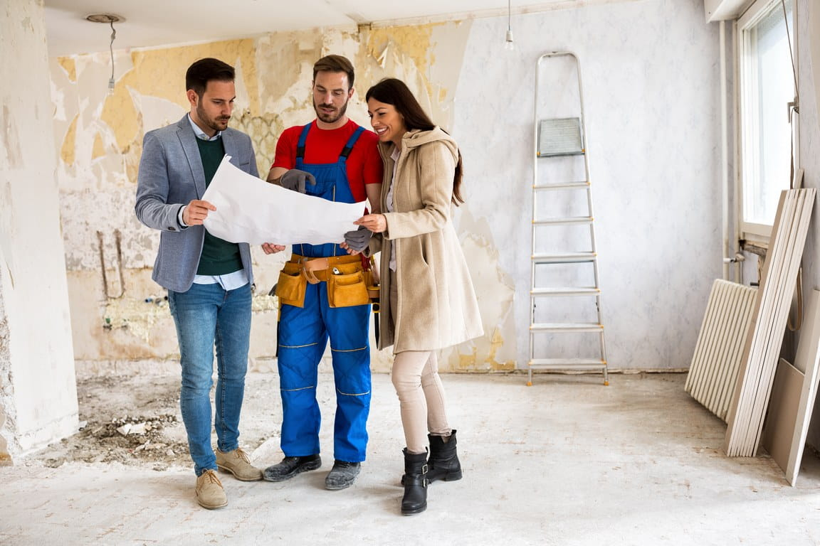 Handyman showing couple a blueprint