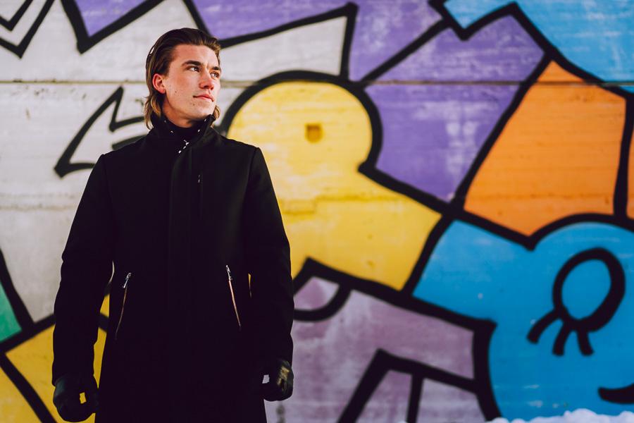 Portrett av mann som står ved en tagget vegg