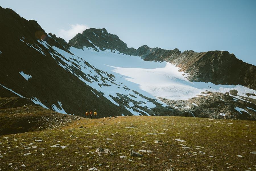 tre personer ser mot en isbre på et fjell i Lyngen