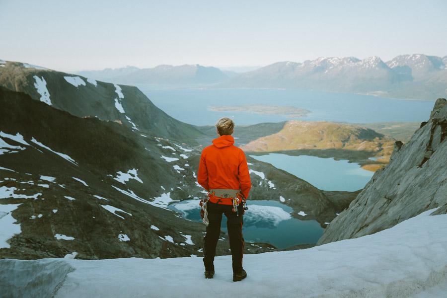 Mann nyter utsikten fra en fjelltopp i Lyngen